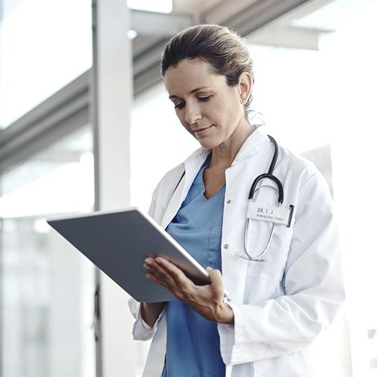Female doctor looking at laptop