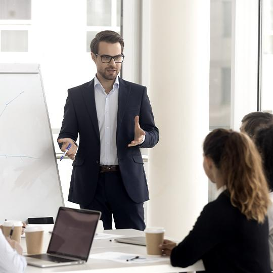 Man giving a presentation in front of white board